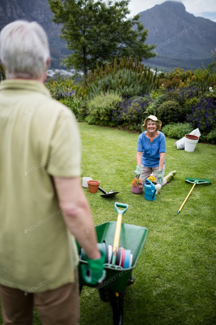 Couple interacting with each other while gardening