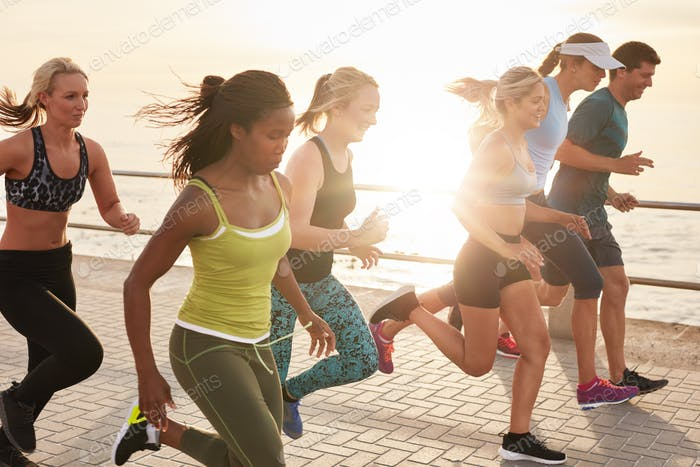 Healthy young people running race on seaside promenade