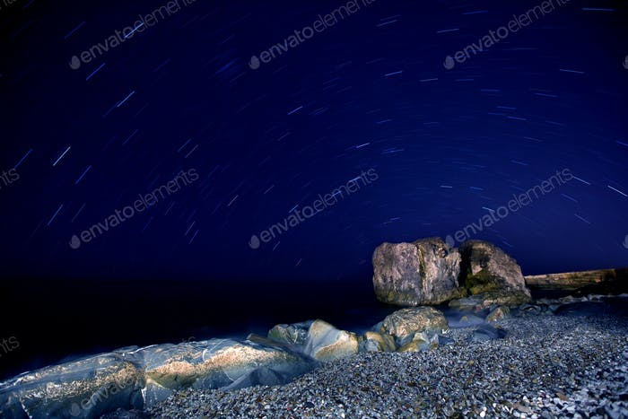 Sea sandy beach with boulders in moon light