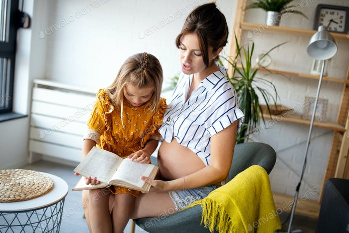 Portrait of pregnant mother and daughter reading a book in living-room