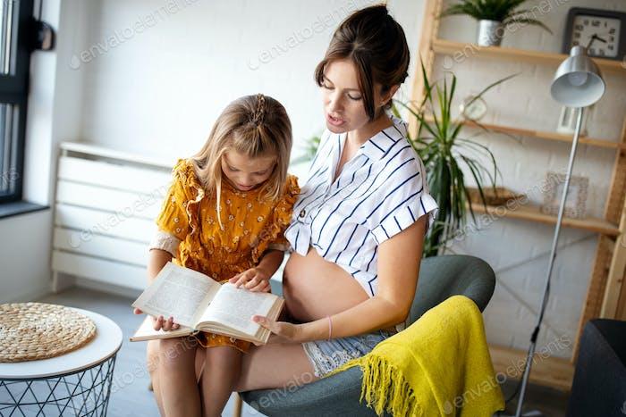 Porträt der schwangeren Mutter und Tochter lesen ein Buch im Wohnzimmer