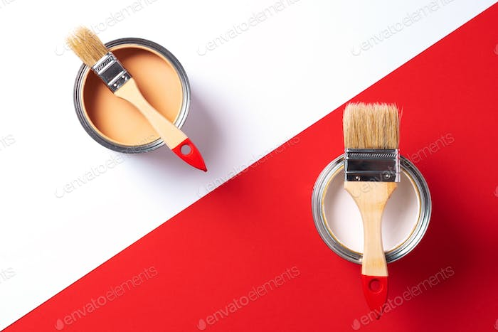 Wooden paint brushes, open paint cans on trendy red and white background. Top view, copy space