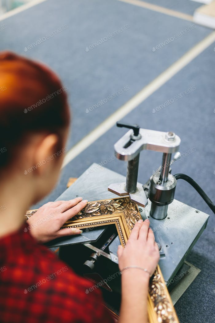 Woman worker sticking together a wooden frame with glue.