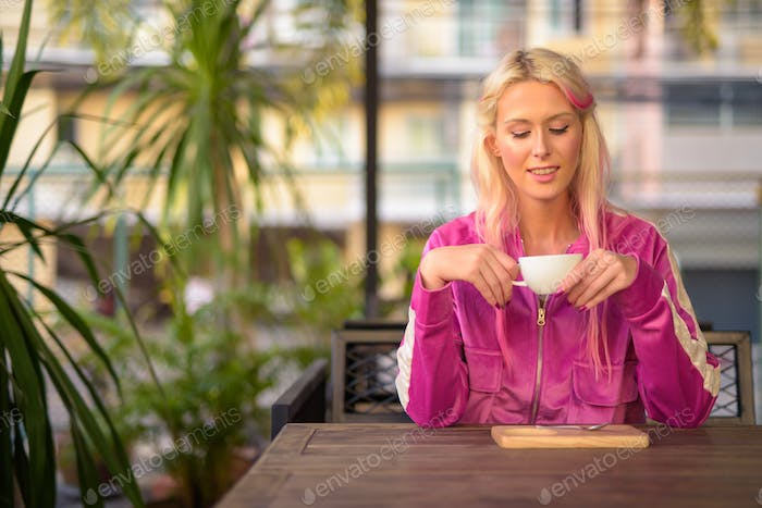 Happy young beautiful blonde woman relaxing at the coffee shop