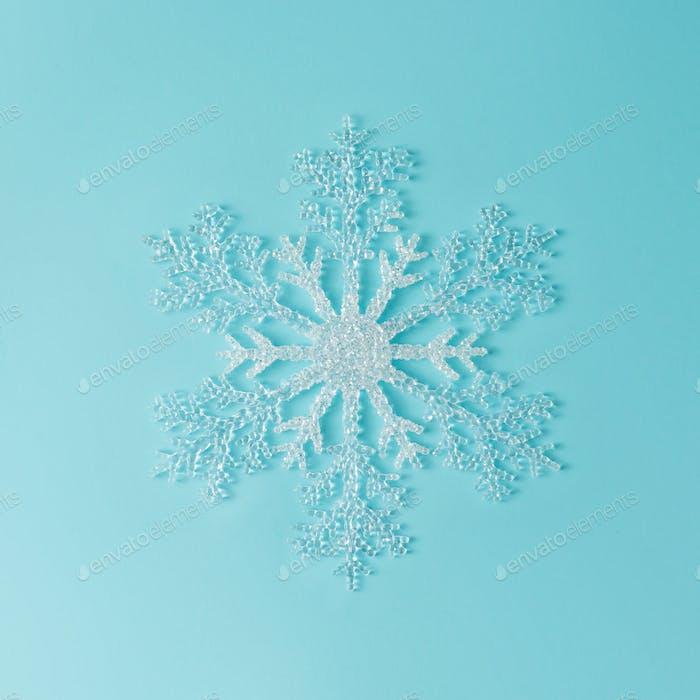 Minimal snowflake on bright blue background. Flat lay. Season concept.