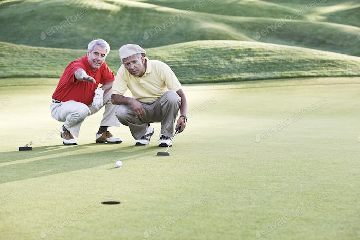 Senior golfers judging the lie on one of the greens of the golf course.