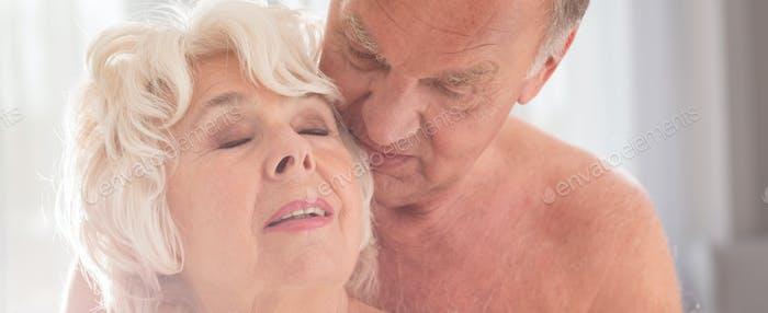Älterer Mann küsst Frau im Kopf