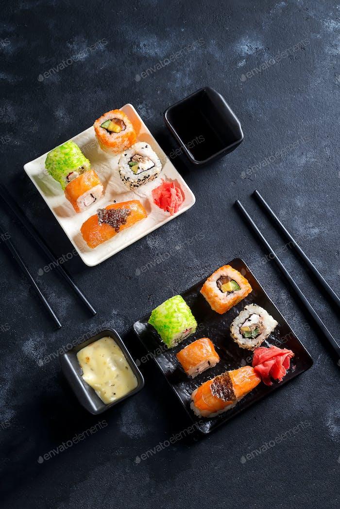 Traditional Japanese food- sushi, rolls, chopsticks, soy sauce on black slate background. Sushi menu