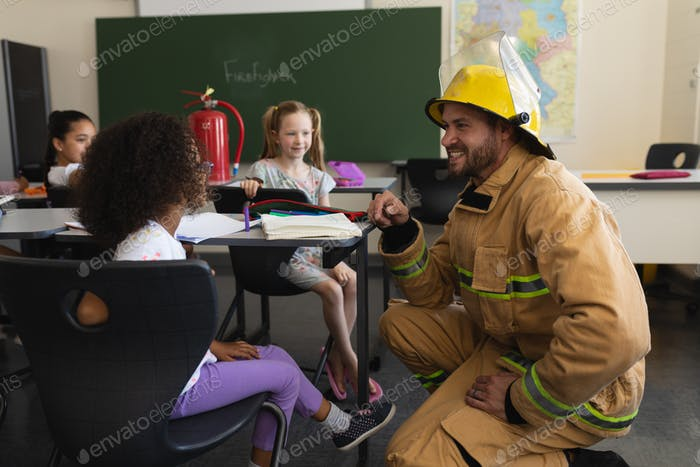 Male firefighter teaching schoolgirls about fire safety in classroom