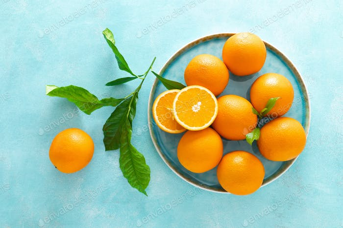 Oranges with leaves on blue background, top view