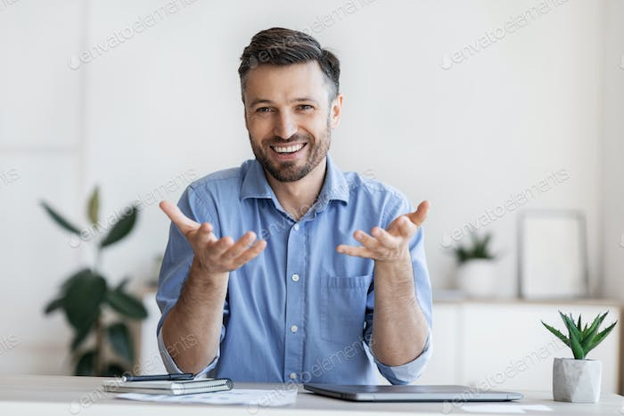 Successful handsome businessman sitting at desk in office, talking at camera