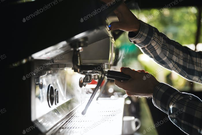 Image closeup of caucasian barista man making coffee while worki