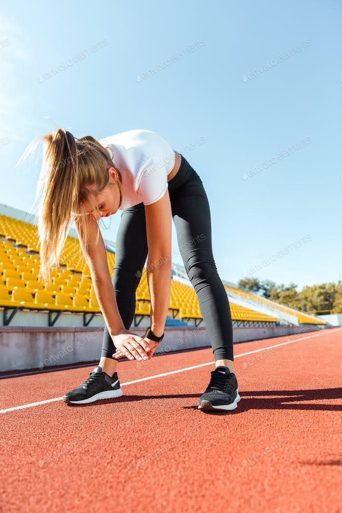 Woman stretching at stadium
