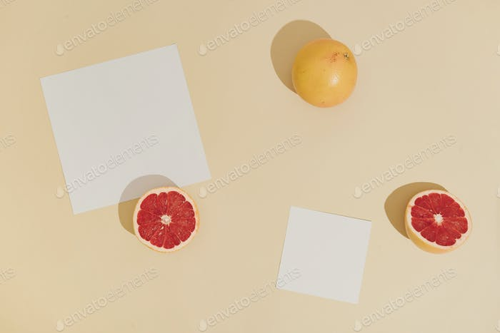 Minimal sunlit fruit composition with sand colour background and sharp shadows.