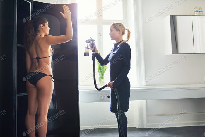 Woman being sprayed with bodypaint during spraytan session