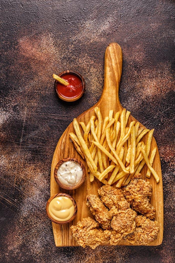 Alitas de  pollo fritas con patatas fritas.