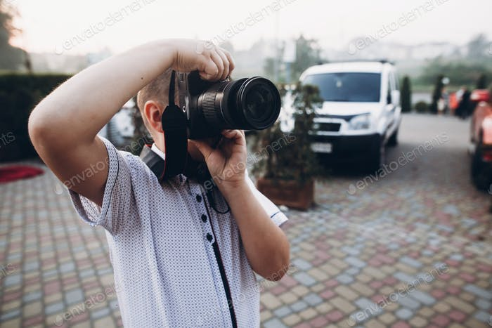 boy holding big photo camera, playing as wedding photographer at wedding reception
