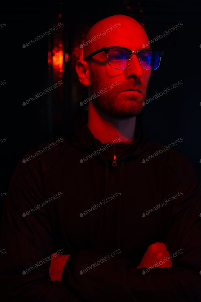 Neon light studio close-up portrait of serious man