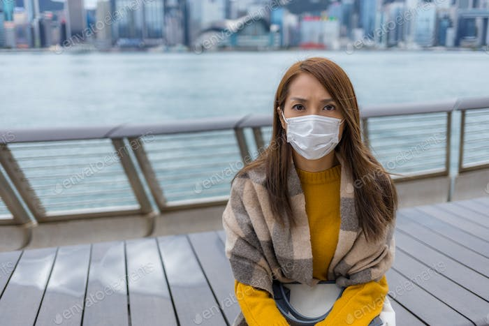Woman wear face mask and sit at the city