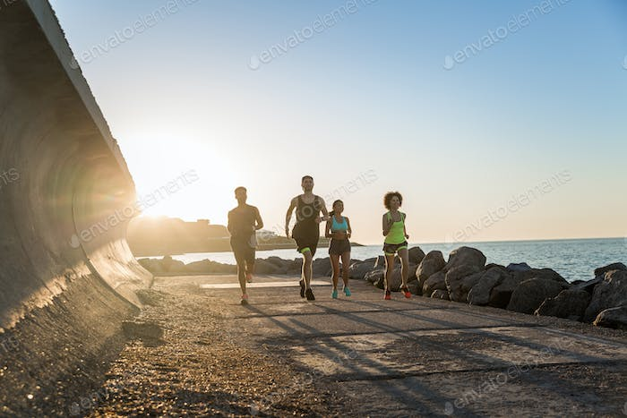Group of young sporty friends jogging together outdoors