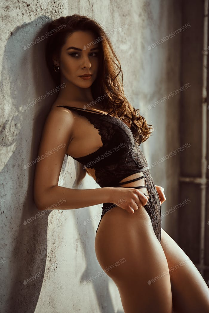 Young female model with dark hair and lace underwear posing in a bright room