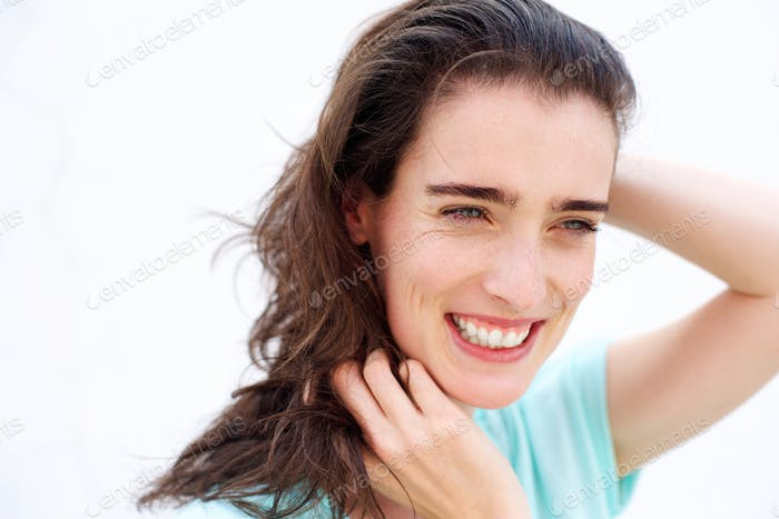 Attractive young lady smiling with hands in hair
