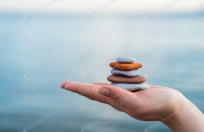 Pile of stacked stones in human hand