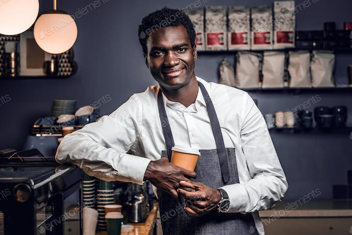 Barista holding a cup with coffee in a coffee shop