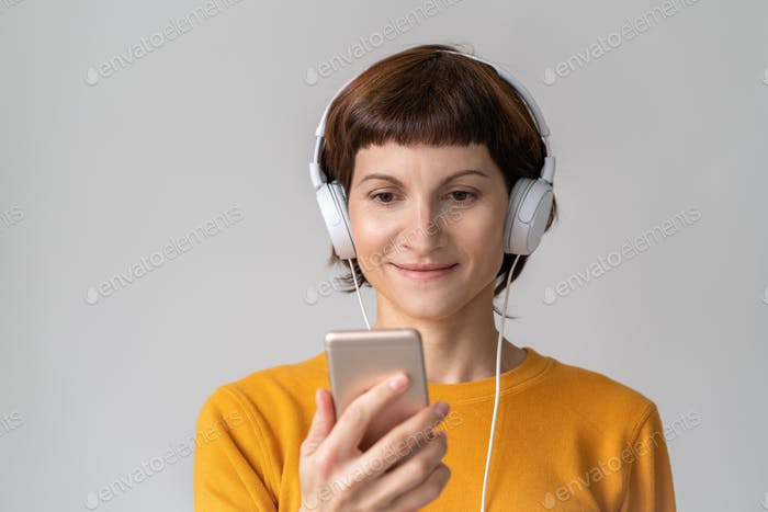 Middle-aged happy woman looking at phone, listening to music. Mature female