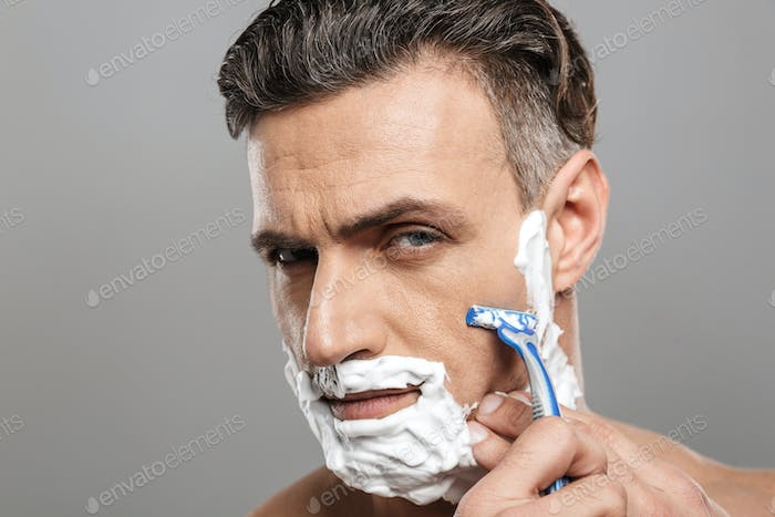 Handsome mature concentrated man naked shaving.