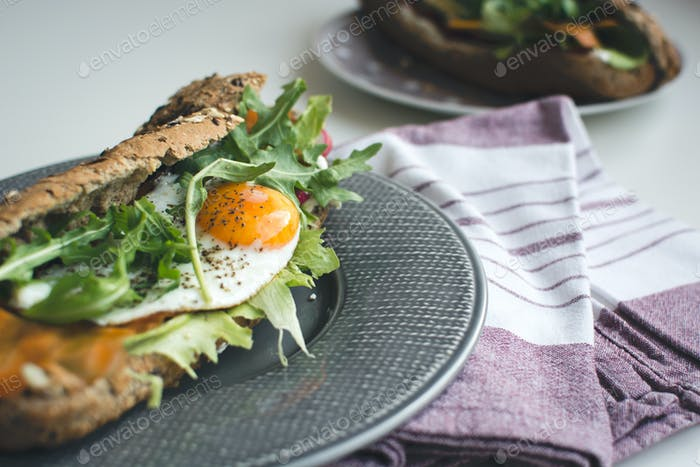 Wholewheat baguette with fried egg and arugula