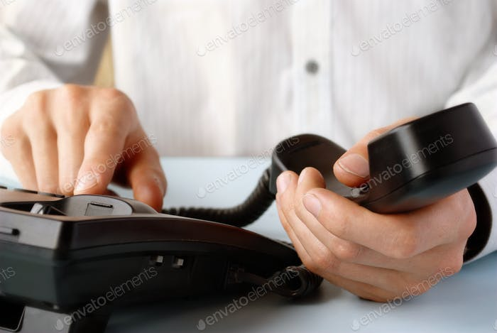 im Büro eines Mannes hält das Telefon