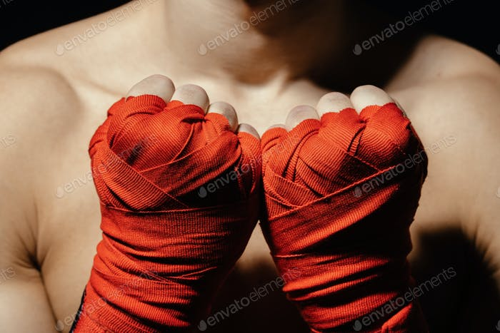 Close up boxer hands in red bandages near the chest