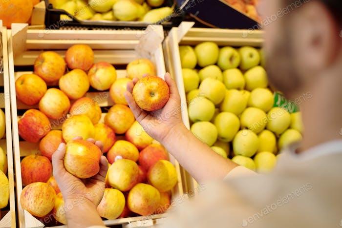 Junger Mann Wahl frische reife gelbe Äpfel im Stehen von Obst Display