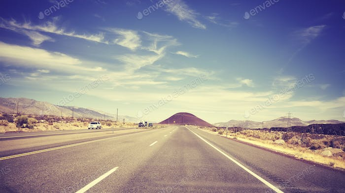 Vintage stylized picture of a highway seen through windshield.