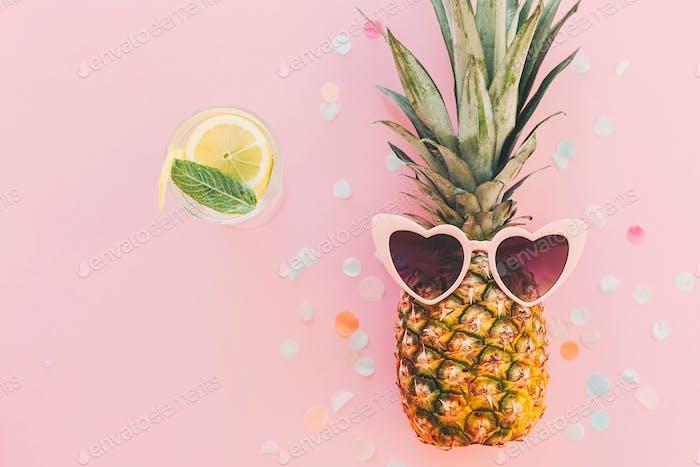 Stilvolle Ananas in rosa Sonnenbrille auf trendigem rosa Papierhintergrund