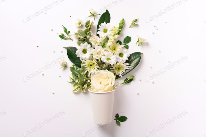 Creative layout made of paper cup with white flowers. Flat lay, top view. Banner with copy space