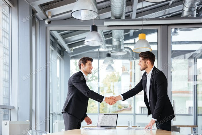 Two happy businessmen standing and shaking hands on business meeting