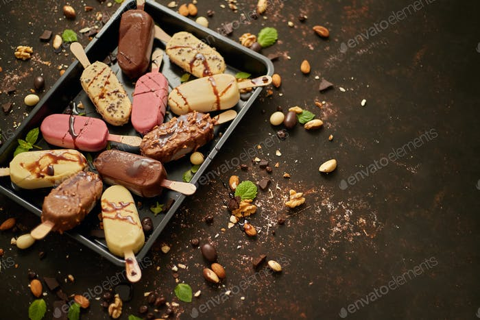 Set of delicious white and milk chocolate and strawberry ice cream on a stick served in metal tray