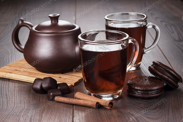 Cup Of Tea With Cinnamon Sticks And Teapot On The Table
