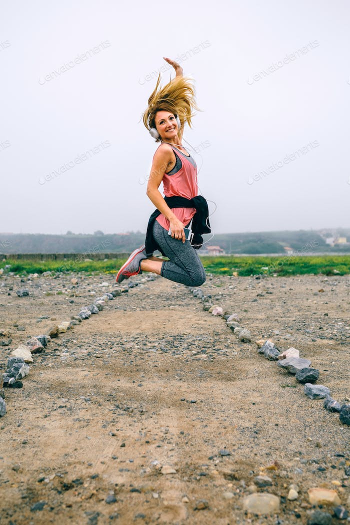 Young sportswoman jumping on the road
