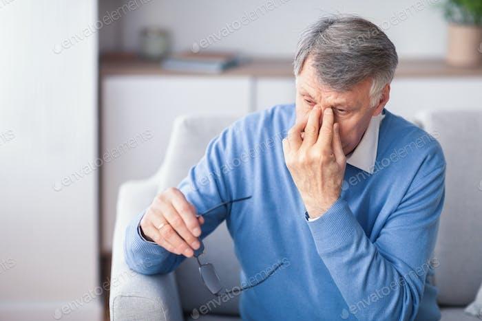 Elderly Man Massaging Nosebridge Sitting On Couch Indoor