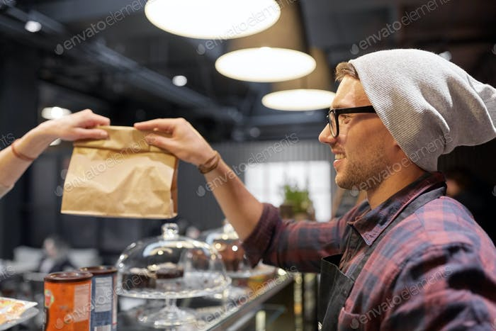 man seller giving paper bag to customer at cafe