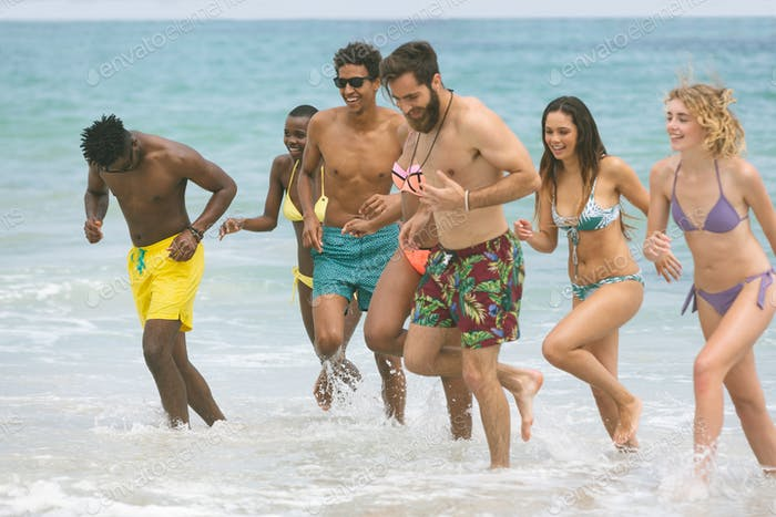 Front view of multi ethnic group of friends enjoying and running on sea at beach on sunny day