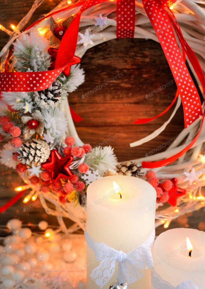 White candles on the snow with Christmas wreath and Christmas li