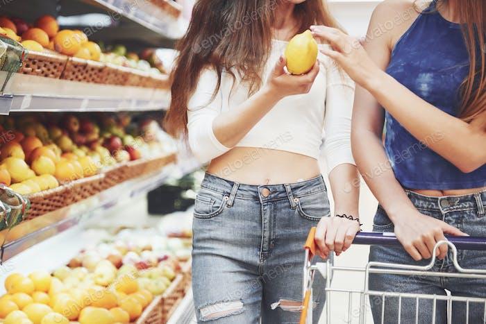 Zwei Frauen wählen saisonale Früchte im Supermarkt Lebensmittelgeschäft