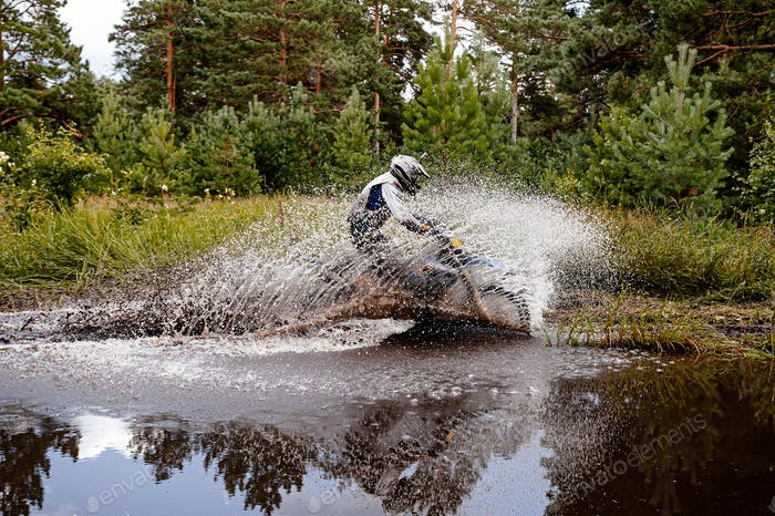 motocross rider riding a puddle in forest trail