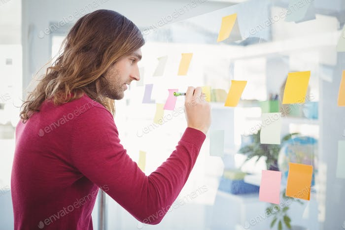 Side view of hipster writing on sticky note stuck on glass in office