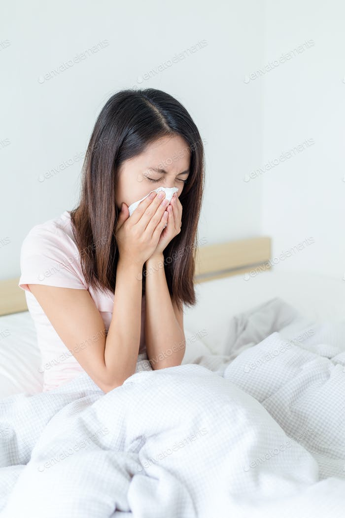 Woman sneeze and sitting on bed