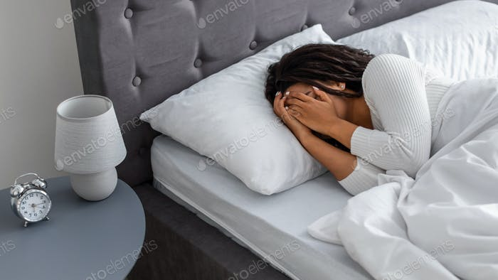 Black woman crying, lying in bed covering face